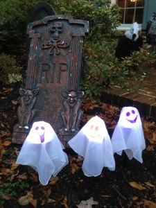 Three ghosts welcoming Trick-or-Treaters on Halloween